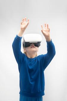Мальчик в очках виртуальной реальности с поднятыми руками