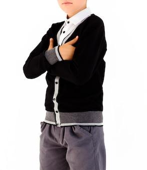 Мальчик в белой рубашке и черном свитере позирует на белом фоне со скрещенными руками
