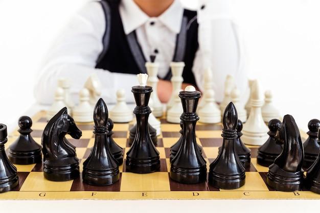 Мальчик в белой рубашке и черном жилете играет в шахматы на белом фоне