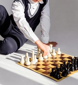 Мальчик в белой рубашке и черном жилете играет в шахматы, сидя на полу на солнце