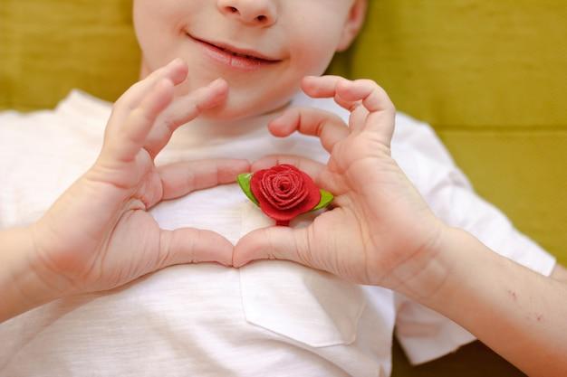 赤いバラの手でハートのシンボルを作る白いtシャツの少年