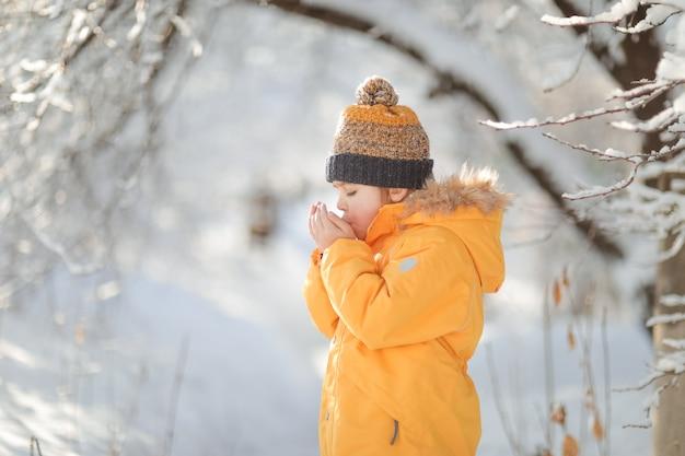 Мальчик в зимнем лесу крупным планом в лесу, играя со снегом