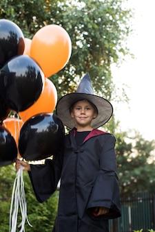 Мальчик в костюме волшебника держит воздушные шары на заднем дворе хэллоуина