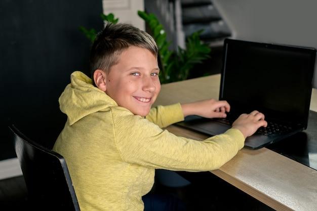 黄色い服を着た少年は、自宅のキッチンの背景にあるコンピューターでオンラインゲームを勉強したりゲームをしたりして笑っている映画を見ています