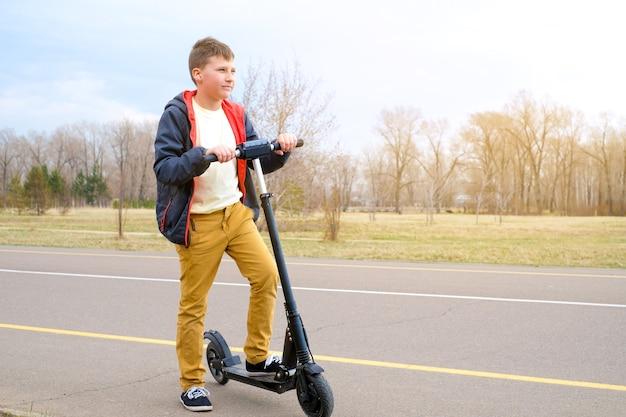 노란색 바지를 입은 소년은 전기 스쿠터와 함께 공원 도로에 있습니다. 봄 화창한 날
