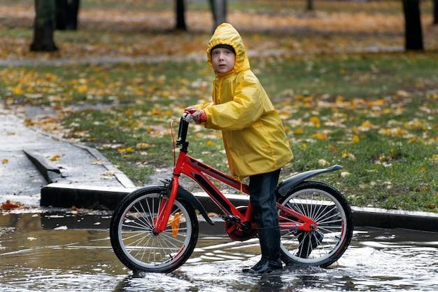 Мальчик в желтом плаще на велосипеде катается по лужам. дождливый осенний день.
