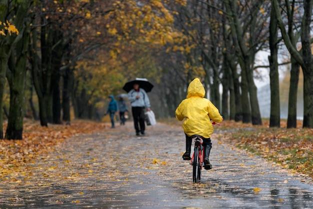 Мальчик в желтом плаще катается на велосипеде по аллее осеннего парка. вид сзади