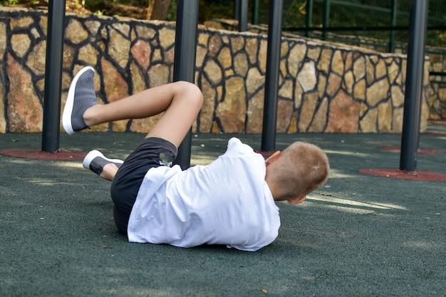 Boy injured on outdoor playground. safety measures on sports ground. trauma bruised child's leg