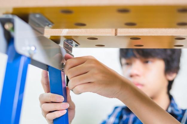 소년은 장인 작업장에 배관의 볼트와 너트를 설치하고 작업자의 손은 볼트의 너트를 조입니다