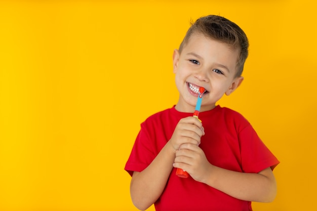 Boy is brushing teeth with toothbrush on yellow background.