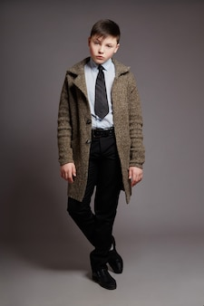 Boy is a businessman in a coat shirt and tie