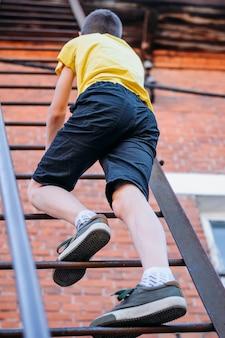 Boy is climbing a high staircase