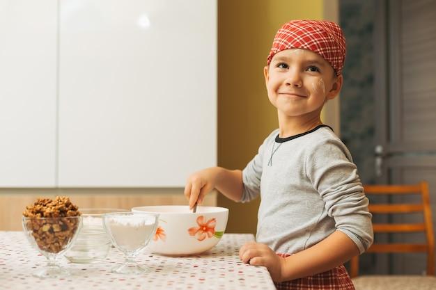 少年は共同しながら食材を混ぜて明るいキッチンで料理をしています