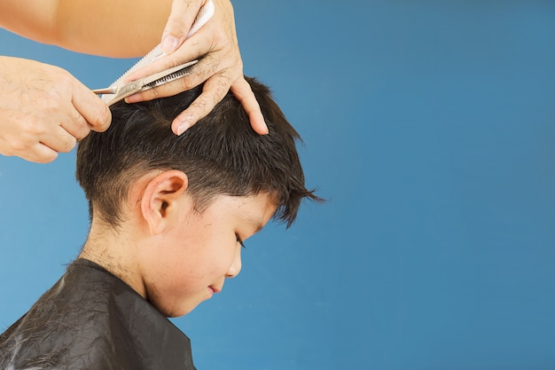 A boy is cut his hair by hair dresser
