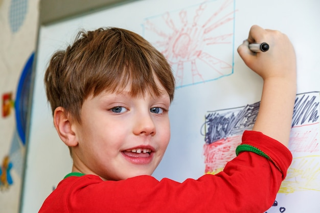 A boy is drawing on a blackboard