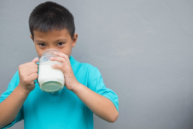 The boy is drinking milk in the glass.