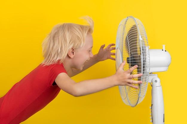 팬의 차가운 공기를 즐기고있는 소년