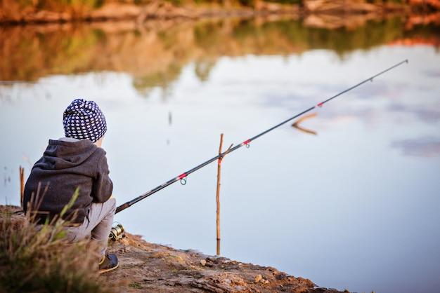 少年は川で釣りをしている。