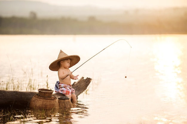 Boy is fishing at sunset on the lake in summer