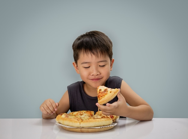 Boy is happy eating pizza with a hot cheese melt stretched on a wooden plate