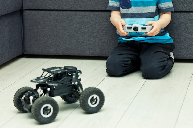Boy is holding joystick and plays with radio control car