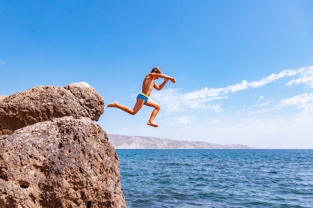 A boy is jumping from the cliff into the sea on a hot summer day. holidays on the beach. the concept of active tourism and recreation