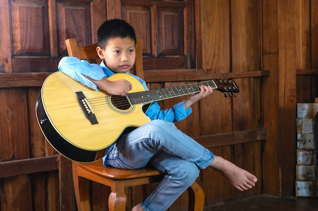 The boy is playing music with his favorite guitar.