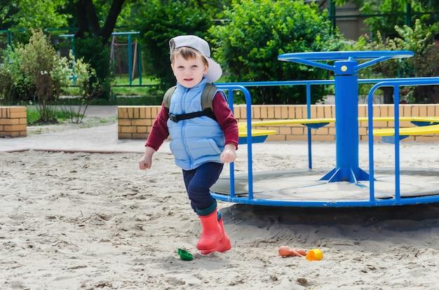 男の子は子供のメリーゴーランドの近くで遊んでいます