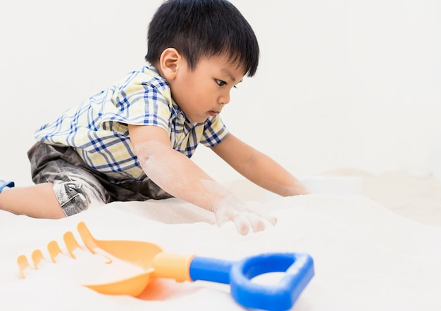 Boy is playing with sandbox toys in educational playground