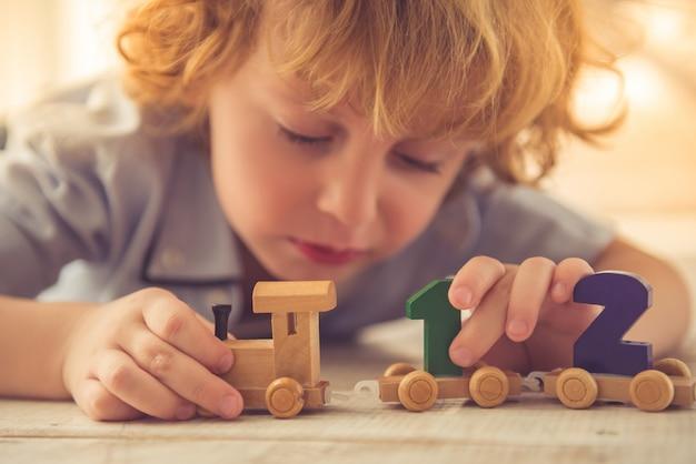 少年はおもちゃの木製電車と自宅で数字で遊んでいます。