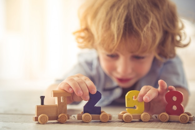 Boy is playing with toy wooden train and numbers at home.