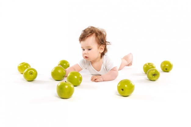 The boy is reaching for apples
