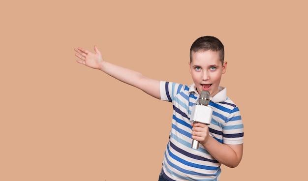 소년은 스튜디오에서 그의 노래를 녹음하고 있습니다. 노래하는 아이가 마이크를 잡고