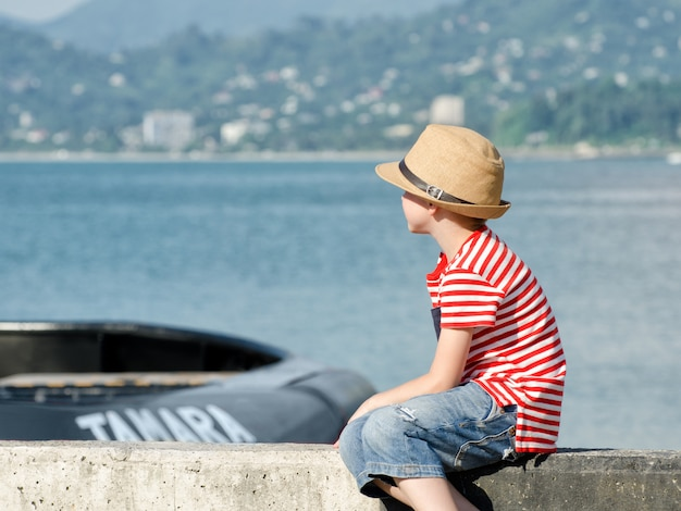 Boy is sitting on the beach with a hat and striped t-shirt, looking at the ship.