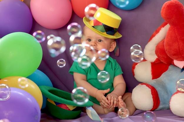 少年は風船で楽しいお祭りの雰囲気の中で座って、シャボン玉を見ています。