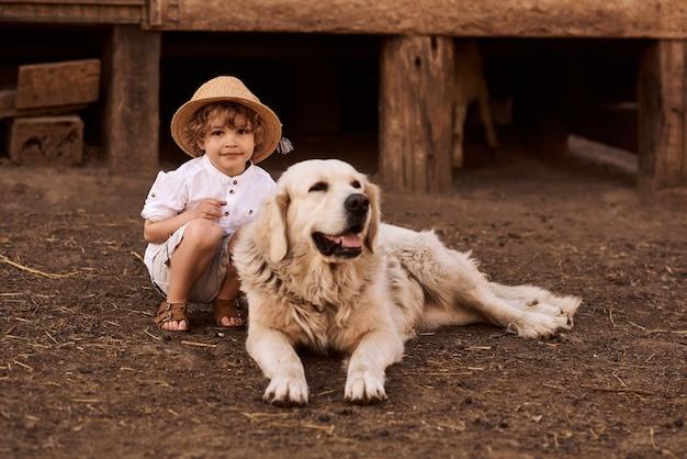 The boy is sitting near the barn hugging a retriever