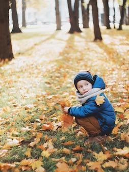 Мальчик сидит на земле и играет с осенними листьями. ребенок собирает букет из листьев