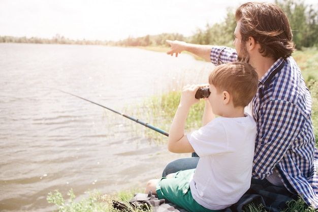 Boy is sitting with his dad at the river shore and looking through binoculars. adult man is pointing forward and holding fish-rod in right hand.