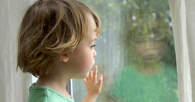 Boy is standing and looking out the window