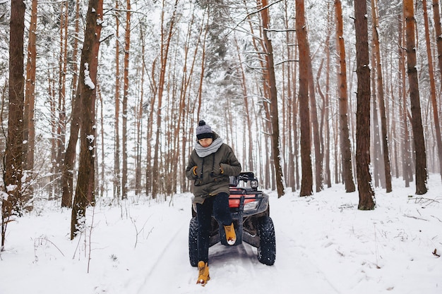 A boy is standing near a quad bike in the middle of the forest