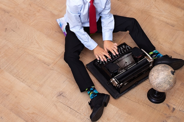 The boy is typing on an old typewriter. schoolboy with a vintage machine. the boy sits on the floor and holds a retro typewriter. close-up of hand of boy as business executive using typewriter. school