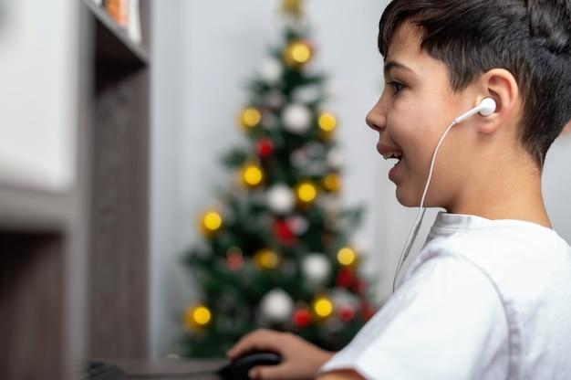 소년은 헤드폰으로 pc를 사용하고 있습니다. 벽에 크리스마스 트리입니다. 행복하고 빠져 나간 얼굴