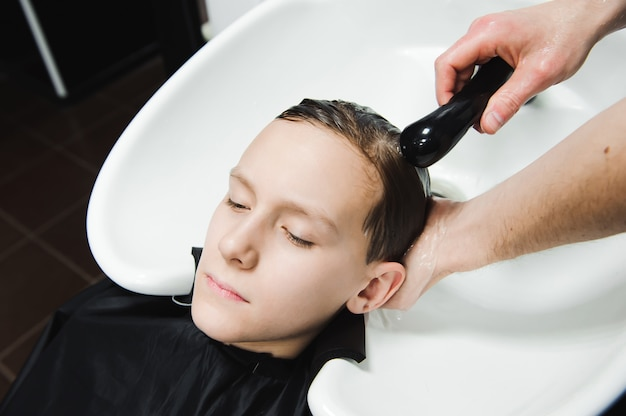 A boy is washed by the hairdresser in the barbershop.