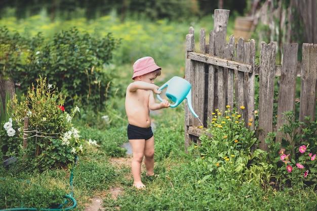 A boy is watering flowers in the garden.