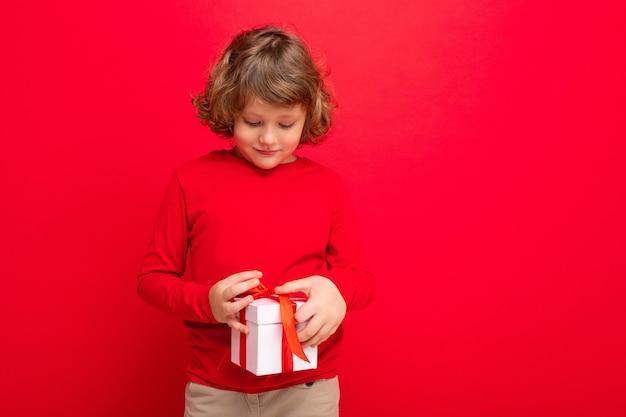 ギフトボックスを保持し、現在のボックスを見て赤いセーターを着て赤い背景の壁に孤立した少年。フリースペース