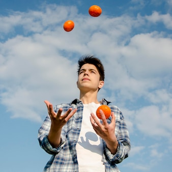 Boy juggles with oranges outdoors