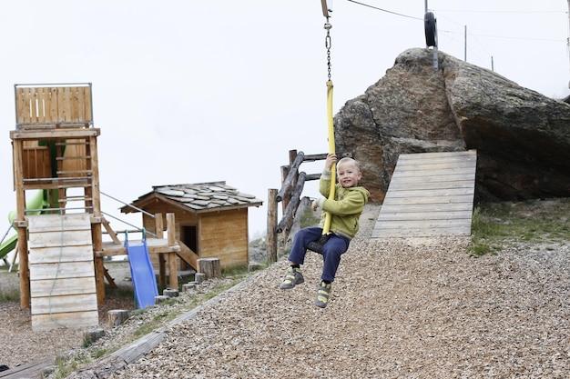산에서 나무에 둘러싸인 자연 놀이 공원에서 지퍼 라인을 점프 소년