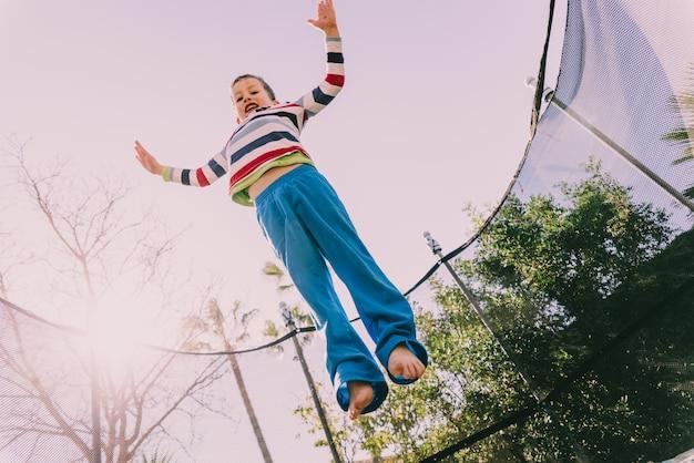 Мальчик прыгает на батуте, осуществляющих на заднем дворе своего дома, наслаждаясь весной с жестом счастья и образа жизни.