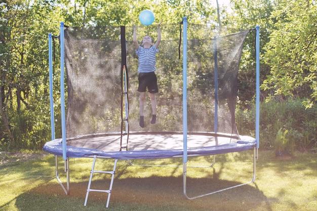 Мальчик прыгает на батуте ребенок играет с мячом на батуте