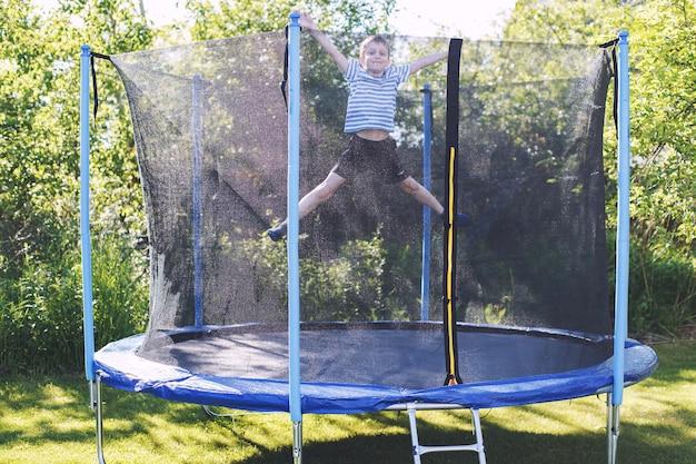 Мальчик прыгает на батуте ребенок играет на батуте на открытом воздухе